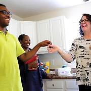Homeowner Christian Pierce, left, and Director of Family Services Jane Roberson share a laugh as Pastor Janice Harris looks on Sunday June 22, 2014 during a Cape Fear Habitat for Humanity dedication ceremony of a recently completed home on Tiffany Drive in Wilmington, N.C. (Jason A. Frizzelle)