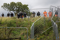 Steeple Claydon, 23rd September, 2020. National Eviction Team enforcement agents and security guards watch tree surgeons working on behalf of HS2 Ltd fell a 200-year-old oak tree alongside the East West Rail route known locally as the '7 Sisters Oak' as part of works connected to the HS2 high-speed rail link. A small group of local people and anti-HS2 activists based at the nearby Poors Piece Conservation Project also observed the felling of the tree, which was home to bats and other species, whilst monitored by a joint force of around fifty bailiffs, security guards and police officers from Thames Valley Police.