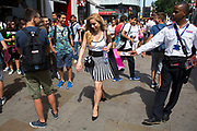 Summertime in London, England, UK. Crowds of tourists and shoppers gather in Leicester Square. This remains one of London's tourism hot spots with entertainers and shop and space to hang out. Woman avoids a bus tour operator handing out leaflets.