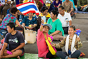 01 SEPTEMBER 2013 - BANGKOK, THAILAND: A woman waves a Thai flag while she listens to speakers at a Siam Pitak anti-government rally Sunday. Siam Pitak is one of several groups organized around opposition to the government of Yingluck Shinawatra, the Prime Minister of Thailand and brother of deposed and exiled former Prime Minister Thaksin Shinawatra, the brother of Yingluck. The Siam Pitak protest has been ongoing in Lumpini Park for more than a month.      PHOTO BY JACK KURTZ