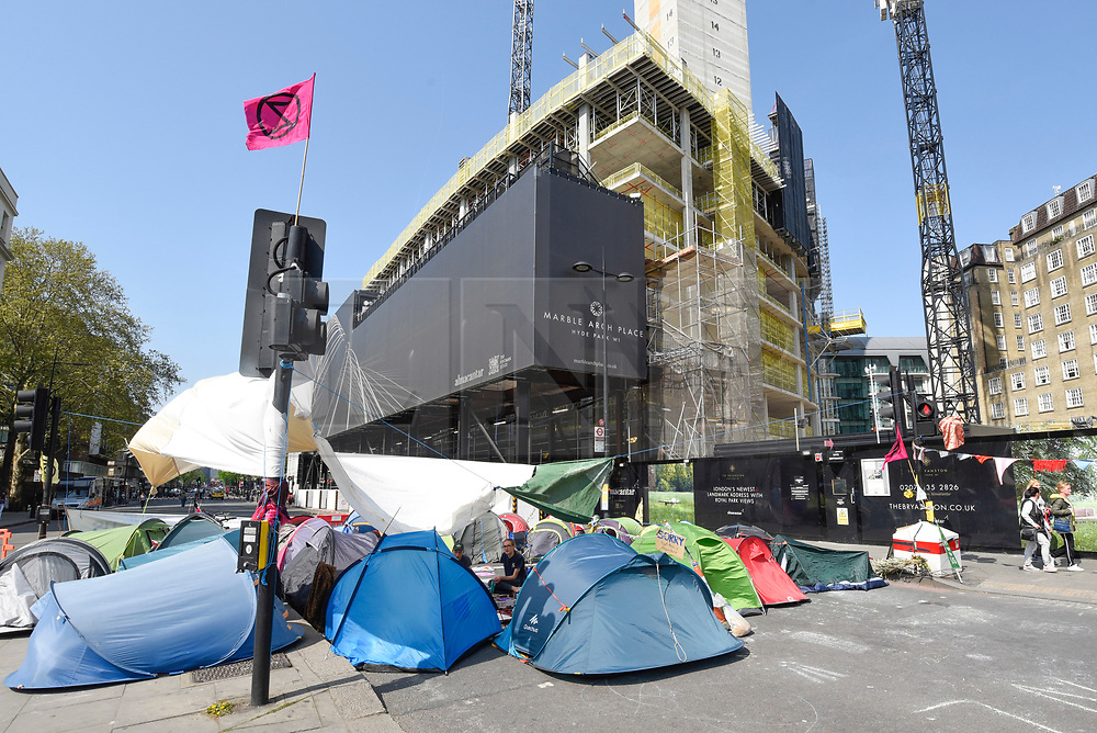 """© Licensed to London News Pictures. 22/04/2019. LONDON, UK.  Activists' tents block the road around Marble Arch during """"London: International Rebellion"""", on day eight of a protest organised by Extinction Rebellion.  Protesters are demanding that governments take action against climate change.  After police issued section 14 orders at the other protest sites of Oxford Circus, Waterloo Bridge and Parliament Square resulting in over 900 arrests, protesters have convened at the designated site of Marble Arch so that the protest can continue.  Photo credit: Stephen Chung/LNP"""