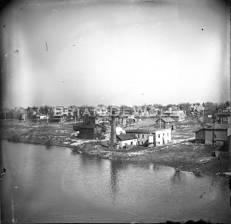 """View looking N.E. from the roof or upper floor of the Newton Wagon Company. Building with the tall chimney also appears in the 1869 """"bird's eye view"""" of map of Batavia.<br /> <br /> The dark building behind (east) of the building complex with the tall chimney still stands in the 100 block N. River directly accross the street from the bike path bridge. State Street would be on lot to the right (south) of that building."""