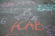 Anti-police chalk messages are seen on the street after a protest march demading justice for Osaze Osagie who was killed by police in 2019.