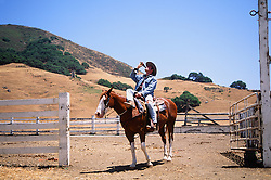 cowboy drinking a coke while sitting on a horse on a ranch in Northern California