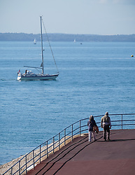 © Licensed to London News Pictures. 09/10/2015. Southsea, Hampshire, UK. A couple enjoy the warm and sunny October weather next to the Solent at Southsea, Hampshire. Photo credit : Rob Arnold/LNP