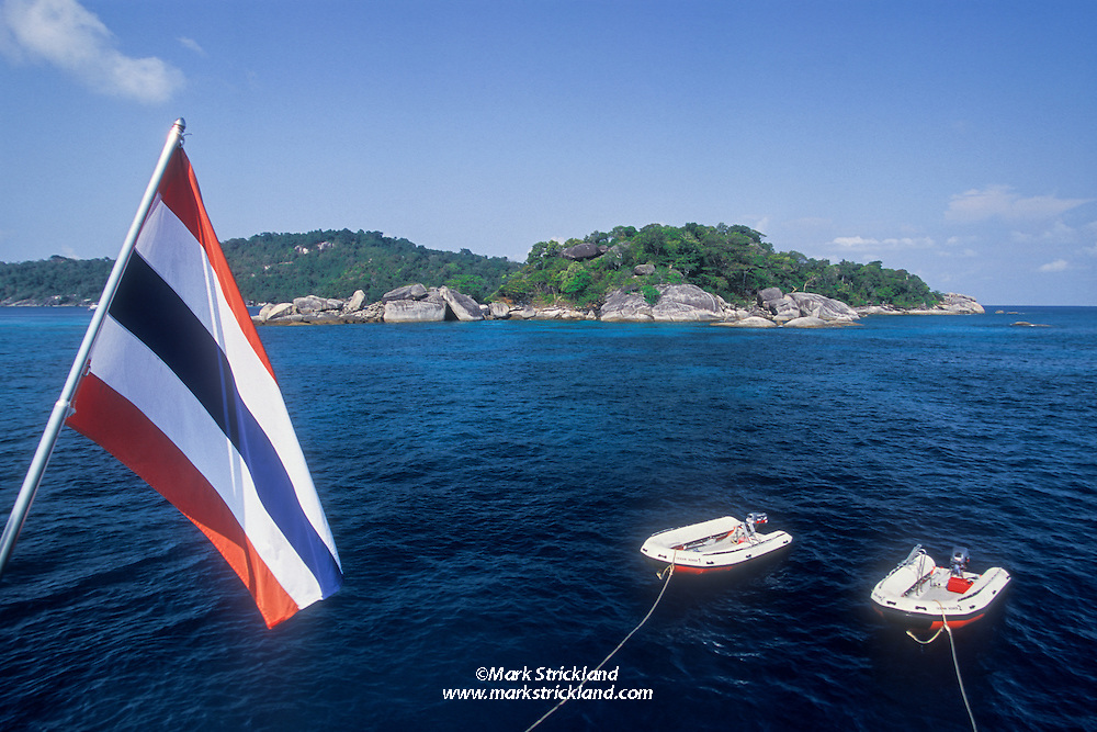 Rocky Islet known as Similan #6, with park headquarters Ko Miang in background, as seen from liveaboard dive boat Ocean Rover. Similan Islands Marine National Park, Thailand, Andaman Sea