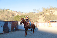 Work Family Guest Ranch, San Miguel, California offers horseback rides through the hills on the 12,000 acre property. Kelly Work and her family wrangling cattle at the ranch in the evening.
