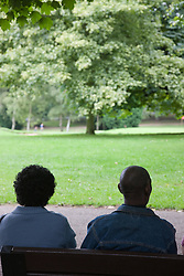 Couple of older people sitting on a bench in the park,