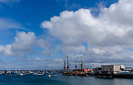 Wide view of Fisherman's Wharf in Monterey, with two tall ships at anchor on a bright spring day.
