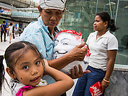 """14 JULY 2013 - BANGKOK, THAILAND:  A child holds onto her mother, who sells """"Guy Fawkes"""" masks to Thai White Mask protesters after a protest in Bangkok Sunday. About 150 members of the so called """"White Mask"""" movement marched through the central shopping district of Bangkok Sunday to call for the resignation of Yingluck Shinawatra, the Prime Minister of Thailand. The White Mask protesters are strong supporters of the Thai monarchy. They claim that Yingluck is acting as a puppet for her brother, former Prime Minister Thaksin Shinawatra, who was deposed by a military coup in 2006 and now lives in exile in Dubai.       PHOTO BY JACK KURTZ"""