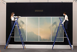 © Licensed to London News Pictures. 23/07/2020. London, UK. Sotheby's staff members hang a painting titled Wolken (fenster) (Clouds (window)) (1970) by artist Gehard Richter with an estimate of £9-12 million. Works spanning over half a millennium of art history go on display at Sotheby's London ahead of a one-off auction on July 28. Titled 'Rembrandt to Richter', the sale will offer the very best from Old Masters, Impressionist & Modern Art, Modern & Post-War British Art and Contemporary Art – travelling from the Italian Renaissance through to Pop Art. Photo embargoed for usage until 24th July 2020 09:00. Photo credit: Ray Tang/LNP