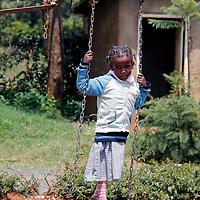 Africa, Kenya, Nanyuki. Girl on swing at the Nanyuki Children's Home.