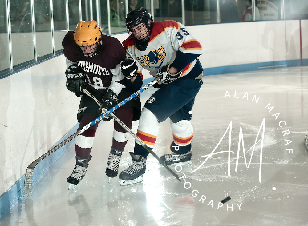 Portsmouth's Wyatt LaPage battles with Belmont-Gilford's Pat O'Connell for control of the puck during Wednesday's game at the Laconia Ice Arena.  (Alan MacRae/for the Citizen)