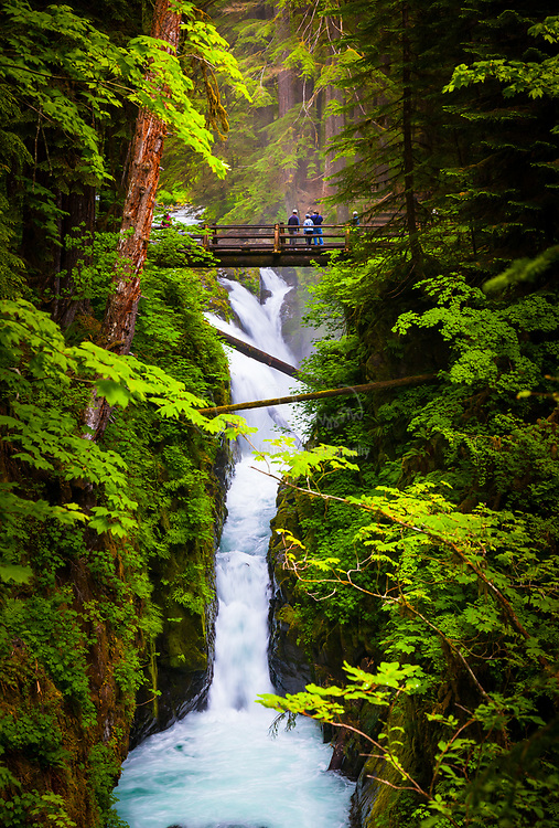 """Sol Duc Falls in Olympic National Park, The name Sol Duc means """"magic waters"""". The Sol Duc River is divided into 3 or 4 separate streams (depending on flow) by an irregular rocky ledge. The water drops about 25 feet over the ledge into a tight cleft, making a 90 degree angle turn. The river passes beneath a footbridge, then drops about 10 feet into a deep teal pool."""