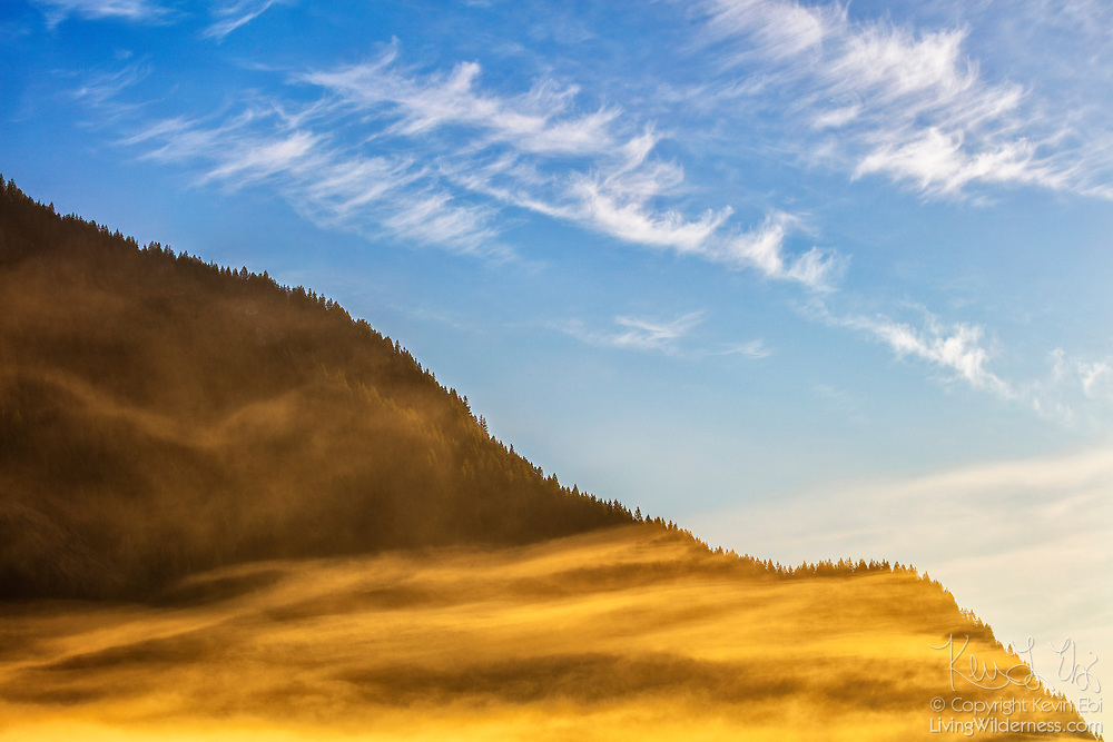 Two layers of water vapor — cirrus clouds and the streaks of a fog bank — frame the flank of Sauk Mountain in Washington state. The mountain is located near the town of Concrete in Skagit County, just west of the crest of the North Cascade Range.
