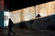 Evening light under an archway creates an interesting light and dark as a figure walks past. East London.