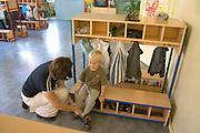 Mom helping son age 28 and 3 put on shoes after Rainbow Preschool Teczowe Przedszkole Balucki District Lodz Central Poland