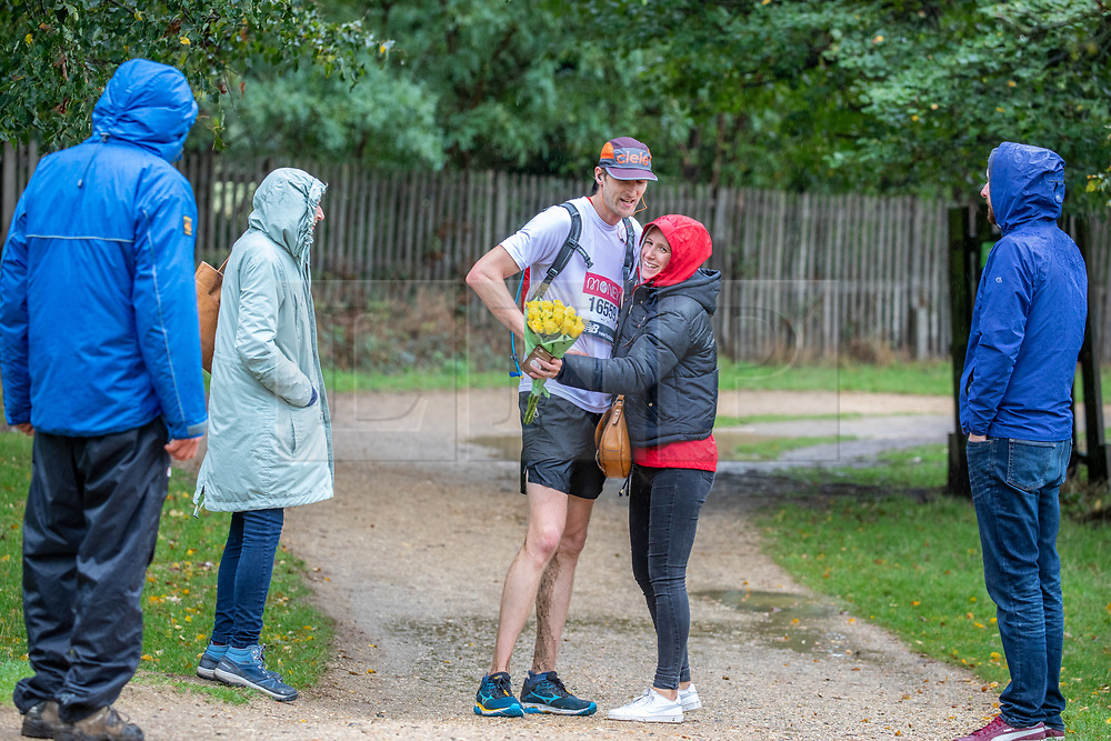 © Licensed to London News Pictures. 04/10/2020. London, UK. A women with flowers congratulates a Marathon runner in Richmond Park in South West London today. The race was postponed until the 4th of October 2020 with over 40,000 people running or walking their own Marathon route due to the coronavirus restrictions. Walkers cyclists and Marathon runners brave the wind and the rain as Storm Alex continues to batter the South East today with 60mph winds and heavy rain as the Met Office issue yellow weather warnings throughout the UK. Photo credit: Alex Lentati/LNP