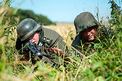 Reenactors portraying a machine gun team from the Panzer Grenadier Division Großdeutschland with an MG42 in its light machine gun role is camouflaged in the tree line between two fields. Both soldiers are wearing the iconic German 'coal scuttle' M42 Steel helmet (Stahlhelm) the one on the right is covered with a Splinter pattern (Splittertarnmuster) camouflage helmet cover