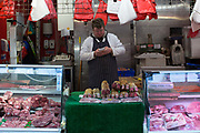 A butcher uses his mobile phone in Brixton Village on 04th January 2017 in London, United Kingdom. Brixton Village has become the destination for budget eating in south London. From the series Our Small World, an observation of our mobile phone obsessions