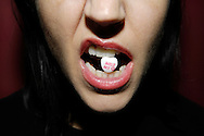 Woman with candy heart in mouth that says Melt My Heart.