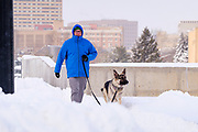 26 JANUARY 2021 - DES MOINES, IOWA: A man walks his dog in fresh snow across the Grand Ave. Bridge in Des Moines. Workers in Des Moines started cleaning up a record snowfall Tuesday morning. The National Weather Service reports that 10.3 inches of snow fell at Des Moines International Airport Monday, January 25, breaking the daily record of 10 inches for January 25 set in 1895. Many downtown businesses closed for the day because of the snow, since roads throughout central Iowa were snowpacked and hard to drive.        PHOTO BY JACK KURTZ