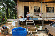 Jumatiah Binti Darmansyah - a smallholder palm oil farmer - sits on the steps in front of her wooden home in Toniting, Beluran District, Sabah, Malaysia, on 8 September 2016. Jumatiah has been farming her small plot 1.75Ha since the 1990s. She has been able to increase her yields since becoming part of the Wild Asia Group scheme, which works with the Roundtable on Sustainable Palm Oil to support Malaysian smallholders to become certified sustainable. This includes improving farm management, reducing their use of pesticides and fertilizers, and increasing yields. Smallholders account for 40% of global palm oil production, and as such play an important role in increasing sustainability within the industry.