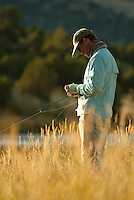 A young man fly-fishes at sunset in northwest Wyoming.