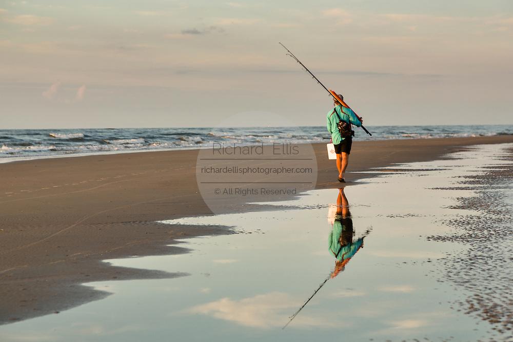 Fishermen walk along the beach at dawn on Isle of Palms at Wild Dunes near Charleston, South Carolina.