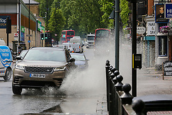 © Licensed to London News Pictures. 24/05/2021. London, UK. A car ploughs through a large puddle of water in north London, with more rain forecast for the South East of England today. Over the May bank holiday, temperatures are expected to reach 21 degrees celsius. Photo credit: Dinendra Haria/LNP