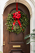 A wooden door on a historic home decorated with a Christmas wreath on Legare Street in Charleston, SC.
