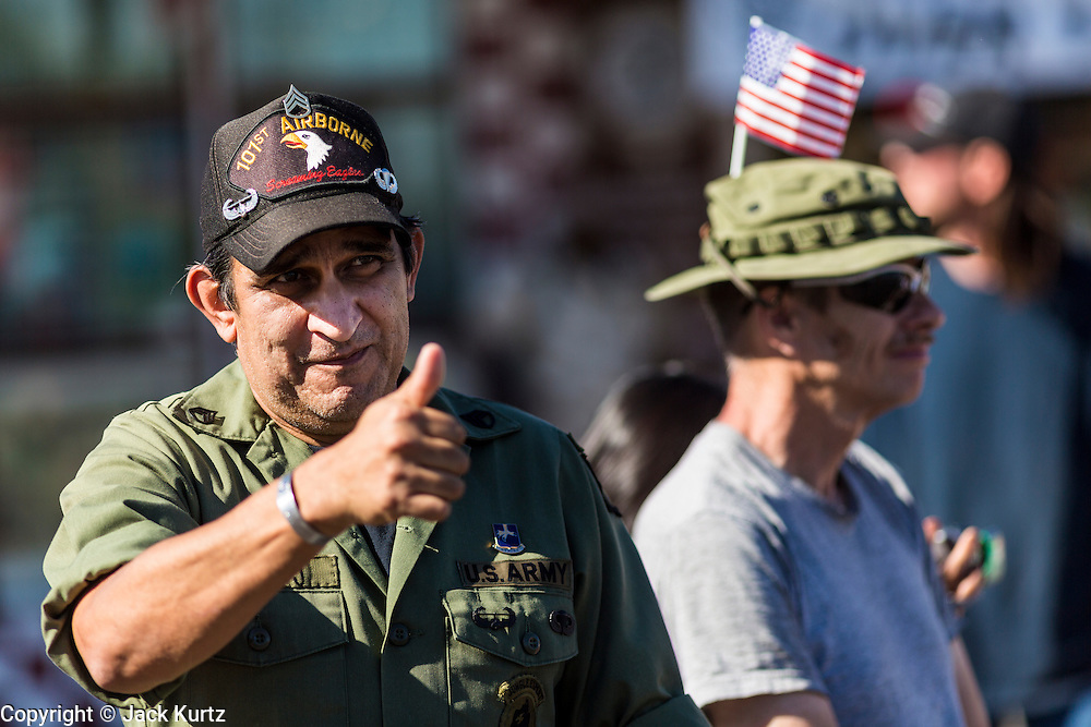 """11 NOVEMBER 2013 - PHOENIX, AZ:  A Vietnam era vet waves to passing veterans at the Phoenix Veterans Day Parade. The Phoenix Veterans Day Parade is one of the largest in the United States. Thousands of people line the 3.5 mile parade route and more than 85 units participate in the parade. The theme of this year's parade is """"saluting America's veterans.""""   PHOTO BY JACK KURTZ"""
