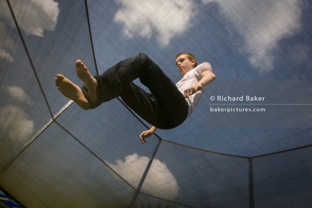 A fifteen year-old teenage boy plays on a family trampoline.