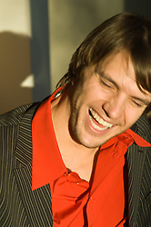 man in a  red shirt and jacket laughing with his eyes closed