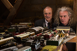 Brothers Simon, 53 and Paul Hurst, 58 have some of their late father's ashes carried around his extensive model railway in the loft of his home. PICTURED: Paul, left and Simon admire the detail in their father's work. Leeds, Kent, March 15 2018.