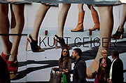 People pass a large fashion poster for Kurt Geiger. Covent Garden in the West End of London.
