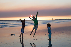 Three kids jumping on beach during sunset, Viana do Castelo, Norte Region, Portugal