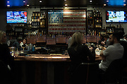 Patrons sit at the bar in The Rustic during a Super Tuesday watch party on March 1, 2016 in Dallas, Texas.  (Cooper Neill for The New York Times)