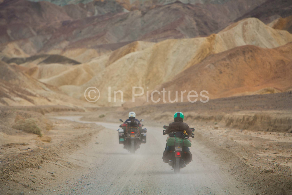 Motorbikes with camping gear on 20 mule team road in Death Valley National Park in California, noted for its erosional landscape and being one of the worlds hottest places.