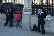 Outside Britain's Palace of Westminster parliament, a young black boy and a Charlie Chaplin character making a Donald trump joke, on the day of Trump's inauguration as the 45th US president, on 20th January, in Parliament Square, London borough of Westminster, England.