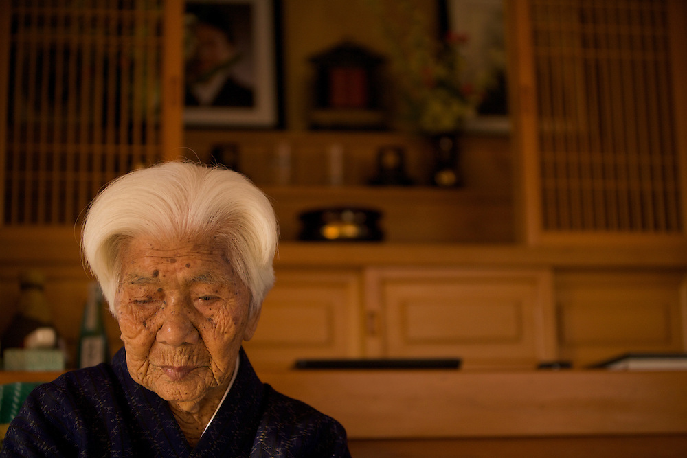 "We traveled to the town of Ogimi and tracked down its most famous inhabitant: Ushi Okushima. Over the past five years this 104-year-old woman has been filmed by every major news organization in the world, including the Discovery Channel, CNN, and the BBC. She's like the Dalai Lama of longevity. ..When we met Ushi, she sat queen-like and serene on a chair in front of a family altar for her ancestors. Wrapped in a blue kimono, she motioned for the team to sit down. Like kindergartners around their teacher, we sat cross-legged on the floor at her feet. And she greeted us by raising her arms above her head, as if to show off her biceps, and shouted, ""Genki! Genki! Genki!"" or ""Vigor! Vigor! Vigor!"" So many people fear getting old. If they could see this woman, they'd look forward to it. ..Ushi still wakes at 6 a.m., makes a breakfast of vegetable miso soup, and goes out for a stroll. Then every afternoon she eats lunch with her daughter, and her grand children and friends come over to visit. In the evenings she eats a dinner of mostly vegetables, drinks a cup of mugwort sake, and goes bed. What's her longevity secret? ""Work hard, drink mugwort sake before bed, and get a good night's sleep,"" Ushi said. ..Actually, asking an old person how she got to be so old is like asking a tall person how she got so tall. They don't really know. But there her life does offer a few clues. For example, Ushi's day is full of social interaction. A Harvard study showed that the seniors with the most social ties were three times less likely to die during the study period than those who had the least social connections. So make time for your family and friends, and you just might add a few years to your life....------------------------------..Ushi Okishima is arguably the most famous centenarian in Okinawa and probably in the world. I met Ushi five years ago while doing an educational project on longevity. My co-leader at the time was a young educational manager by the name of Sayoko Ogata. ."