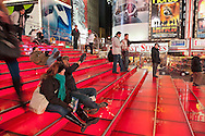 Times Square big Red Stairway, TKTS, with visitors taking their pictures, looking at Broadway billboards, in Manhattan, New York, USA, on January 9, 2012