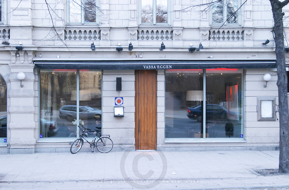 The front windows of the high class gastronomic restaurant Vassa Eggen (the sharp edge) with a bicycle parked outside. Cars reflected in the windows. Better to take the bike if you go dining and drinking Stockholm, Sweden, Sverige, Europe
