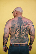 """Scott Mathis, 38, an oil well site manager, wears his heritage on his skin with two oil derricks and a crop duster tattooed to his back. Mathis is a fourth generation oil field worker. His grandfathers and a great-grandfather were all oil drilling hands. """"I was born with like 10 years experience,"""" Mathis said."""