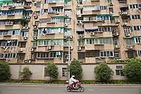 Woman riding an electric bike by an apartment building in Hangzhou, China.