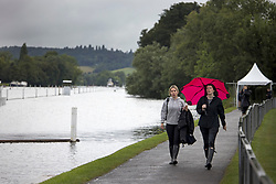 © Licensed to London News Pictures. 09/08/2021. Henley-on-Thames, UK. Members if the public shelter underneath an umbrella as they walk along the bank of the River Thames, ahead of the the Henley Royal Regatta which starts on Wednesday. Established in 1839, the five day international rowing event, raced over a course of 2,112 meters (1 mile 550 yards), is considered an important part of the English social season. Photo credit: Ben Cawthra/LNP