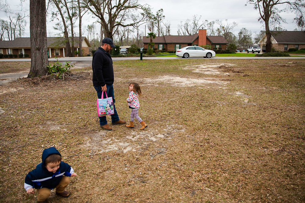 Melissa Sims drives away in the background as her husband, Joe Sims ant their two children, Eli and Alexis, stand by in their yard in Marianna, Fla., on Saturday, Jan. 5, 2019.The couple both works at the Federal Correctional Institute in Marianna, but are having to take turns working for weeks at a time at the federal prison in Yazoo City, Miss, a nearly 7-hour drive. Photo by Kevin D. Liles for The New York Times