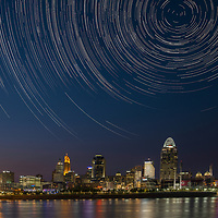 Cincinnati Skyline at night with the city lights reflected on the waters of the Ohio River. This image is a composite of two images. The first image taken shortly after sunset exposing for the buildings and reflections on the water. The second image was taken approximately and hour and a half later from the exact same location using a two-and-one-half hour exposure for the sky and stars. These two images were then blended in the digital darkroom post capture. Polaris was positioned above the Great American tiara. The long exposure highlights the earth's rotation and its effect on the position of the stars in the night sky.
