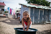 Young girl helping to  wash clothes for the family by hand and outside because of the lack of electricity in this particular Roma area of Frumusani.