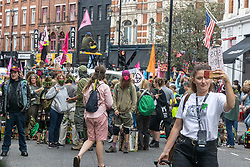 """Licensed to London News Pictures. 23/08/202. London, UK. A heavy police presence in Westminster as climate change protesters Extinction Rebellion (XR) block St Martin's Lane in Covent Garden, London at the start of a 14 day protest with disruptive action and possible occupations of buildings and services. The protest, """"The Impossible Rebellion"""", want the government to implement their demand to stop all new fossil fuel investment immediately. Photo credit: Alex Lentati/LNP"""